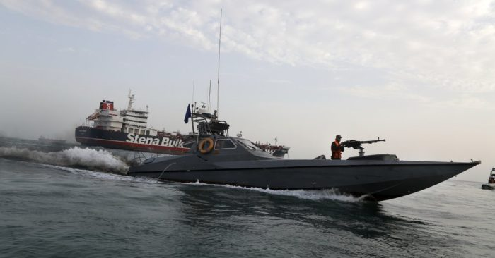 FILE - In this July 21, 2019 file photo, a speedboat of the Iran's Revolutionary Guard moves around a British-flagged oil tanker, the Stena Impero, which was seized by the Guard, in the Iranian port of Bandar Abbas. (Hasan Shirvani/Mizan News Agency via AP, File)